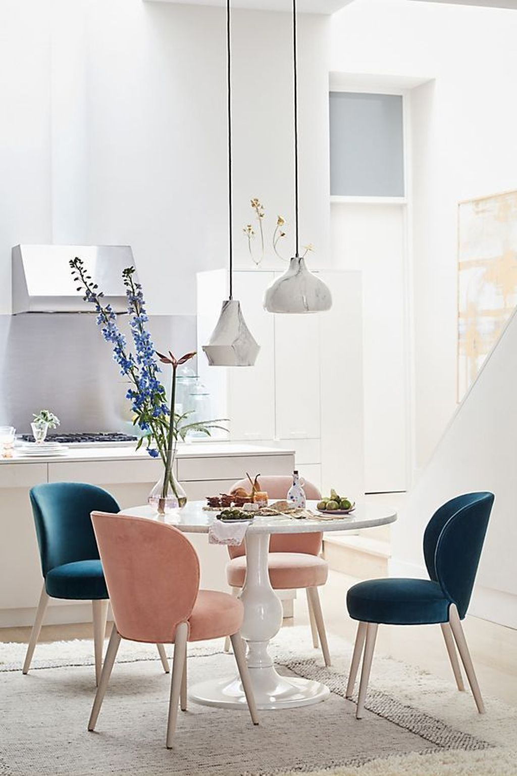 dining room, wooden floor, white wall, white pendants, white round table, pink blue modern chairs, white kitchen cabinet