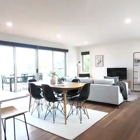 dining room, wooden floor, white wall, white sofa, wooden cabinet, wooden dining table, black modern chairs, white rug