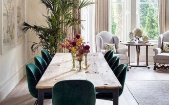 dining room, wooden floor, white wall, wooden dining table, green velvet chairs, white chairs, round table, rug, golden pendant