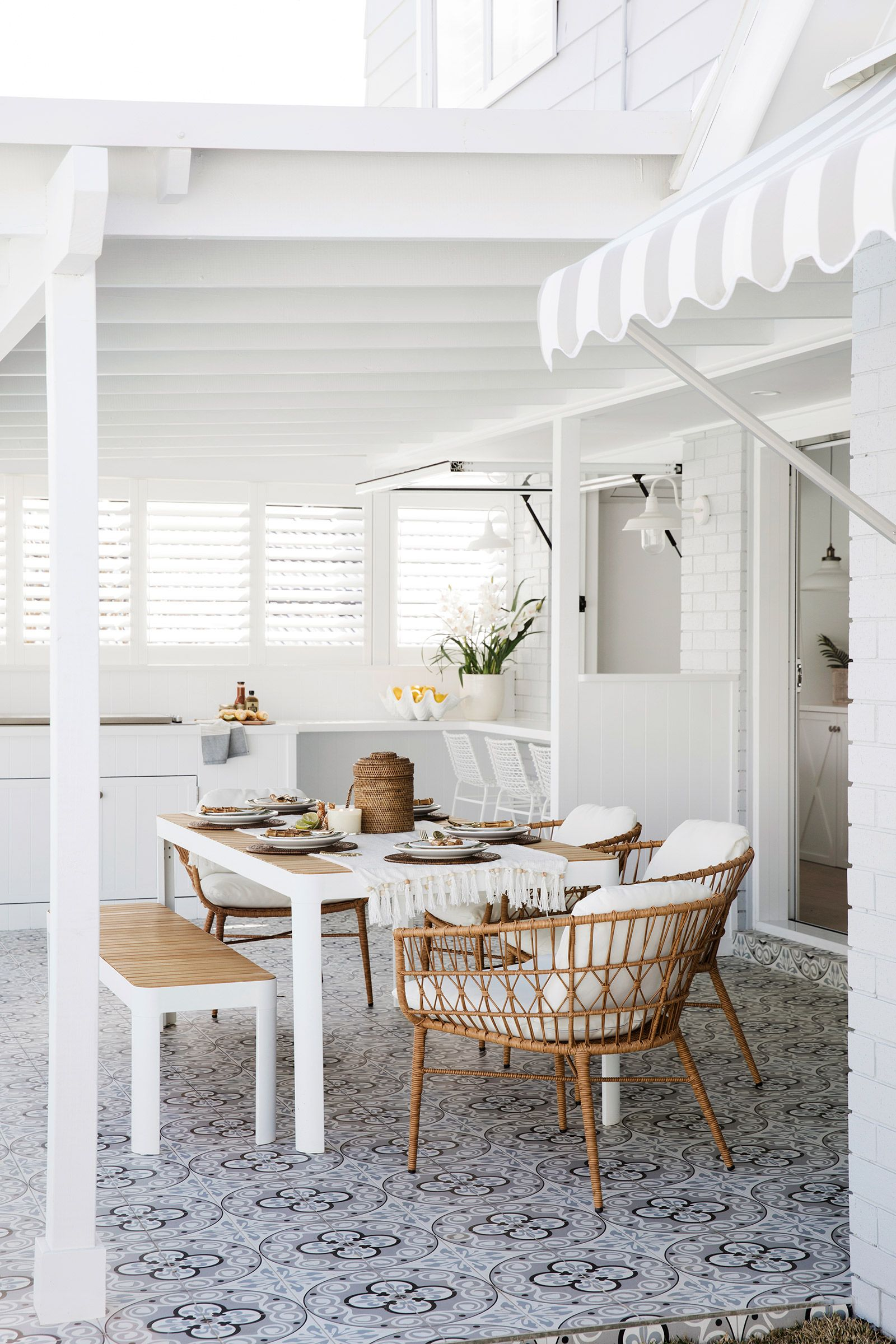 dining set, wooden table, wooden bench, rattan chairs, patterned floor, white wall
