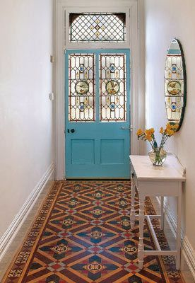 entrance, patterned floor, white wall, blue doors, colorful glass, white console table, round mirror