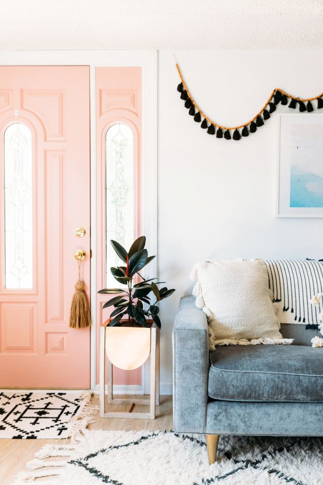 entrance, pink door, white wall, blue velvet sofa, wooden floor, side pot