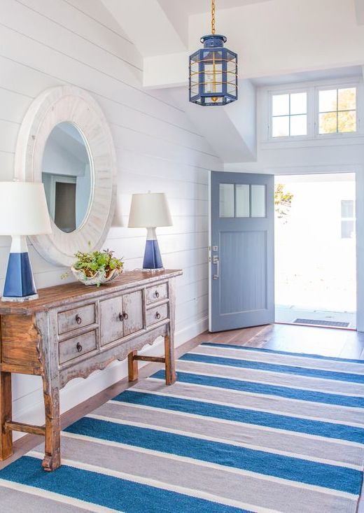 entrance, white shiplank wall, blue wooden door, wooden floor, wooden cabinet, white framed round mirror, white blue floor lamp, blue ironed pendant
