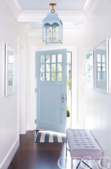 entrance, white wall, wooden floor, blue wooden door, blue pendant, light blue tufted bench