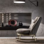 Grey Velvet Rocking Chair, Grey Concrete Wall, Grey Concrete Floor, Rattan Rug, Grey Sconces, Black Nook