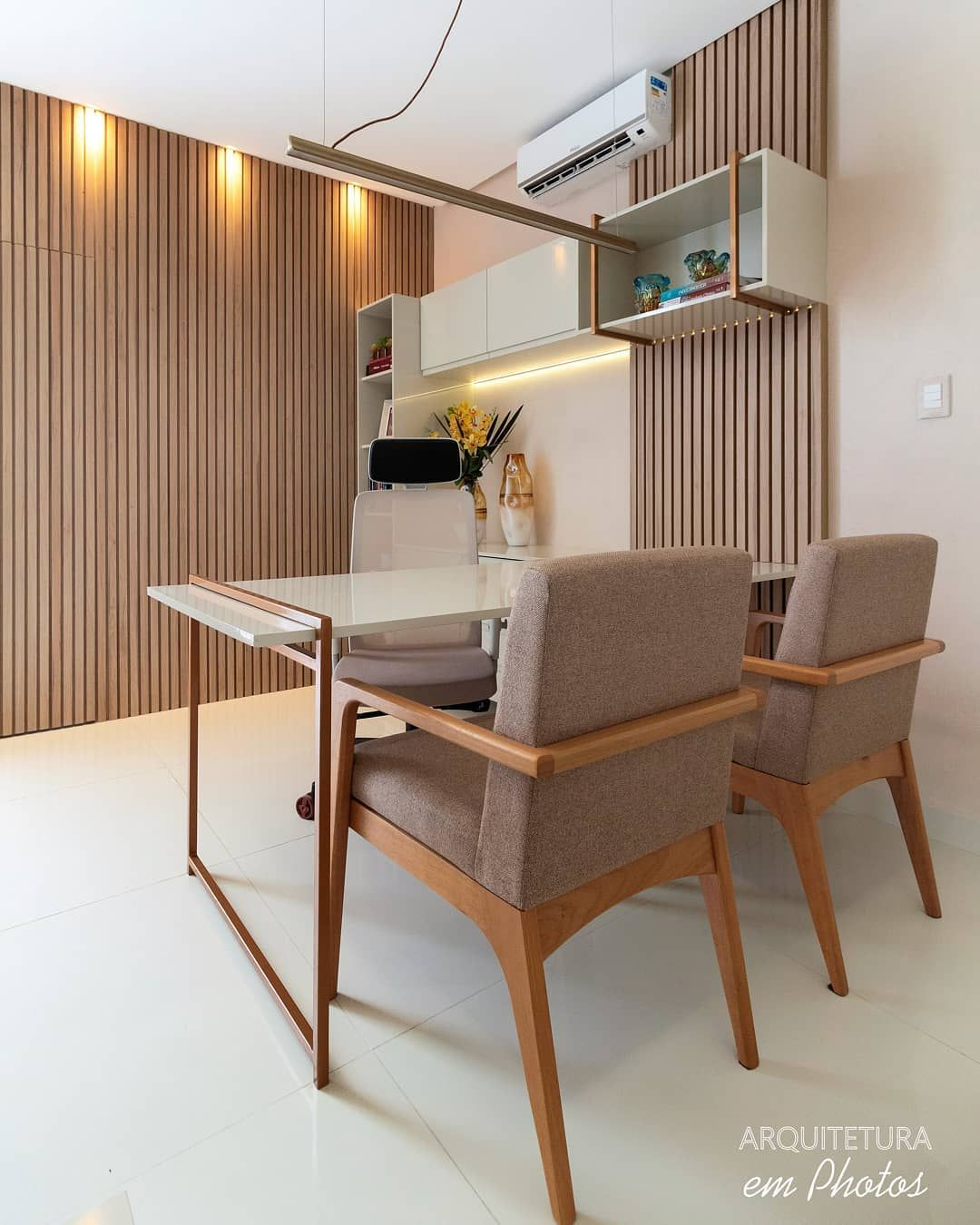 home office, white floor tiles, wooden grid wall, white wall, white table with wooden frame, wooden chairs with brown cushion, white floating shelves