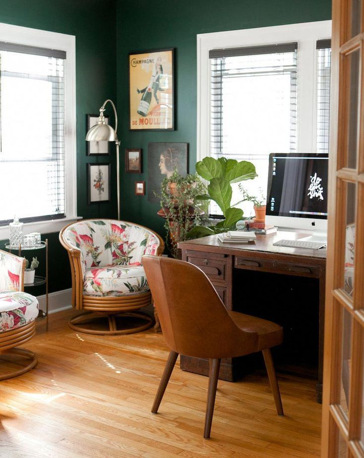 home office, wooden floor, green wall, wooden table, brown leather chair, rattan chair with flowery cushion