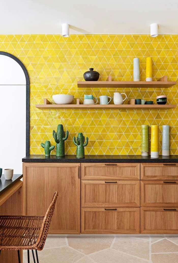 kitchen, brown floor tiles, white wall, yellow wall tiles backsplash, wooden kitchen cabinet with black marble top, wooden floating shelves