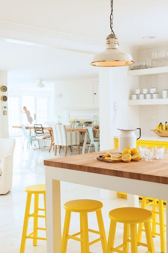 kitchen, white floor, white wall, wooden table, yellow stools