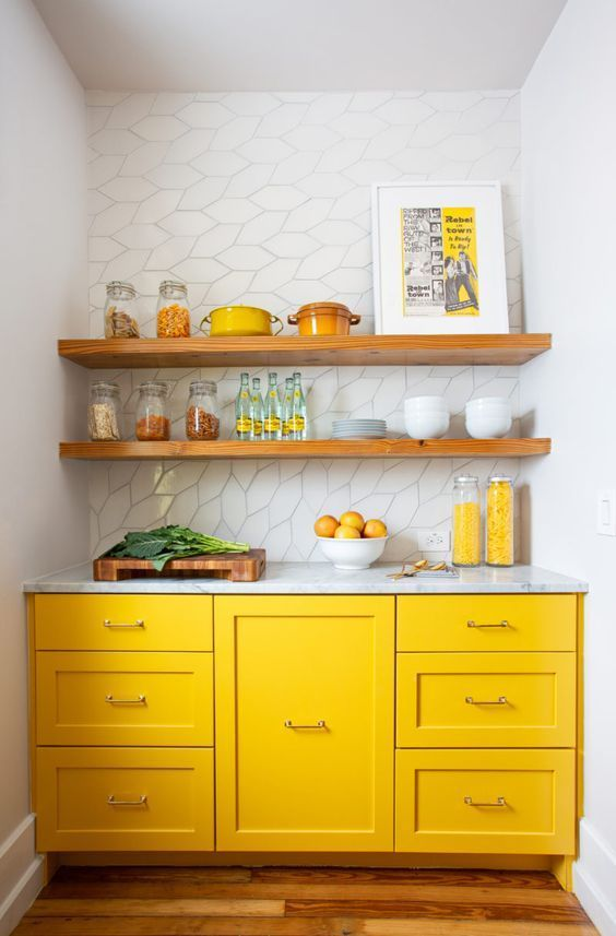 kitchen, wooden floor, white wall, yellow ktchen cabinet, white marble top, white backsplash tile, wooden floating shelves