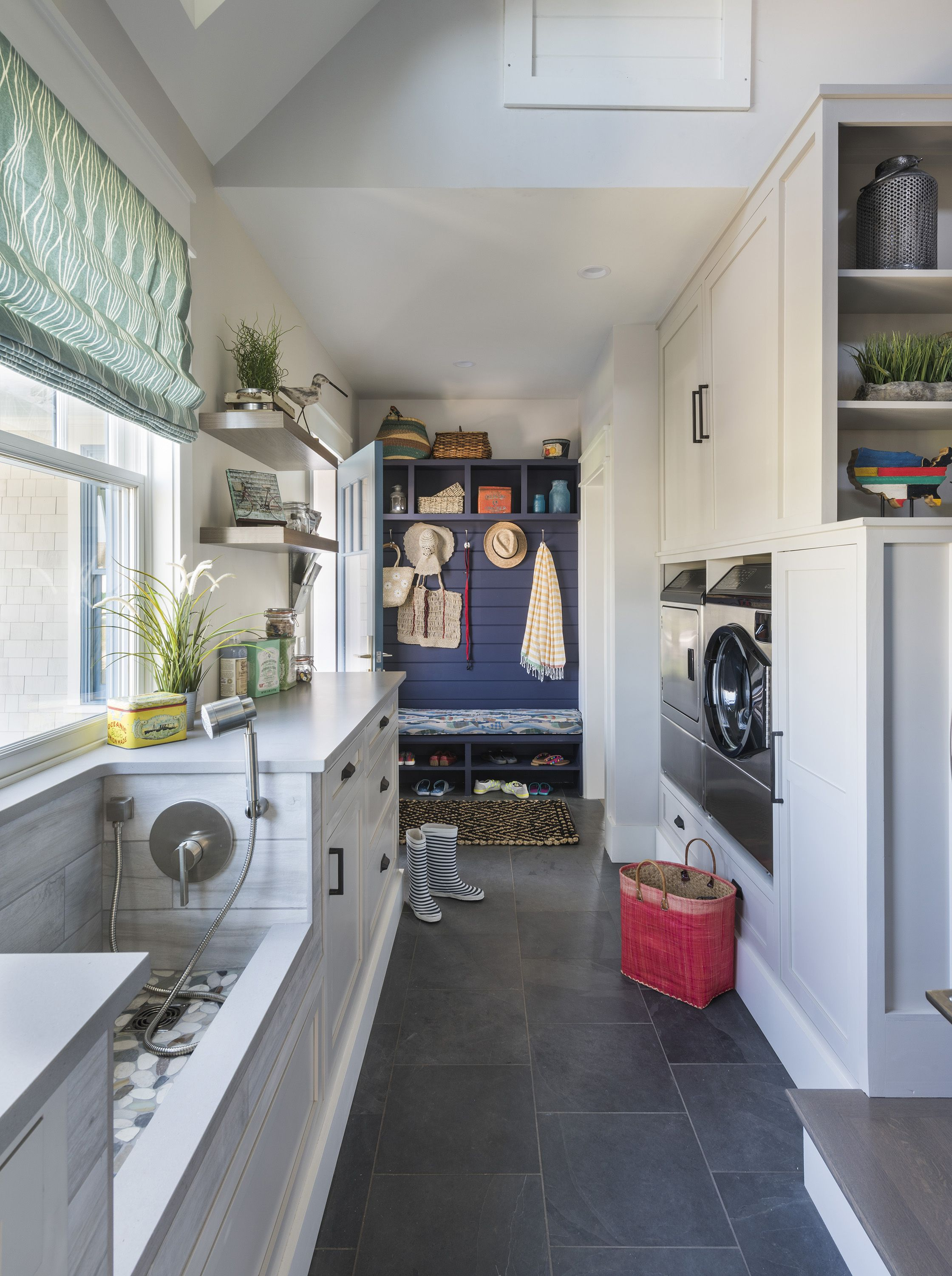 laundry room, grey floorm white wall, white cabinet, white big sink, blue accent wall, bench, washing machine