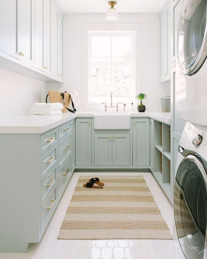 laundry room, white floor, white wall, light green cabinet, white top, white apron sink, white washing machine, white short pendant