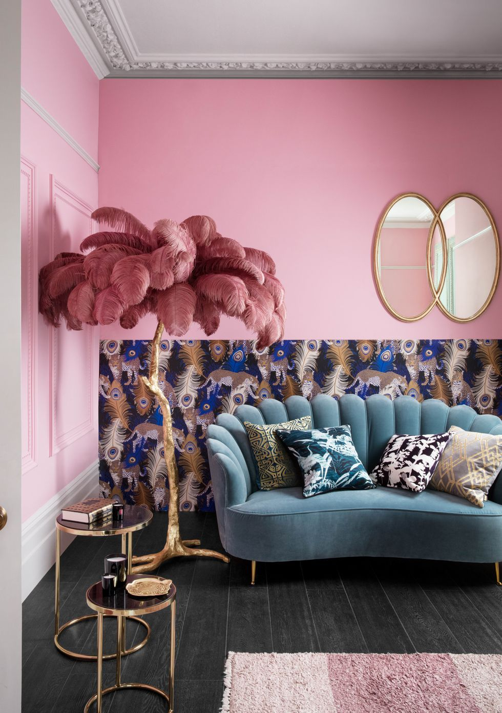 living room, black wooden floor, blue velvet sofa, pink wall, patterned wall, mirrors, golden nesting side table
