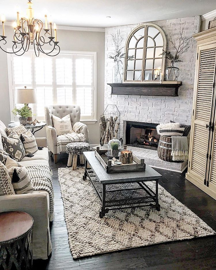 living room, black wooden floor, patterned rug, black coffee table, white exposed brick wall, white tufted chair, white sofa, fireplace, chandelier, wooden cabinet