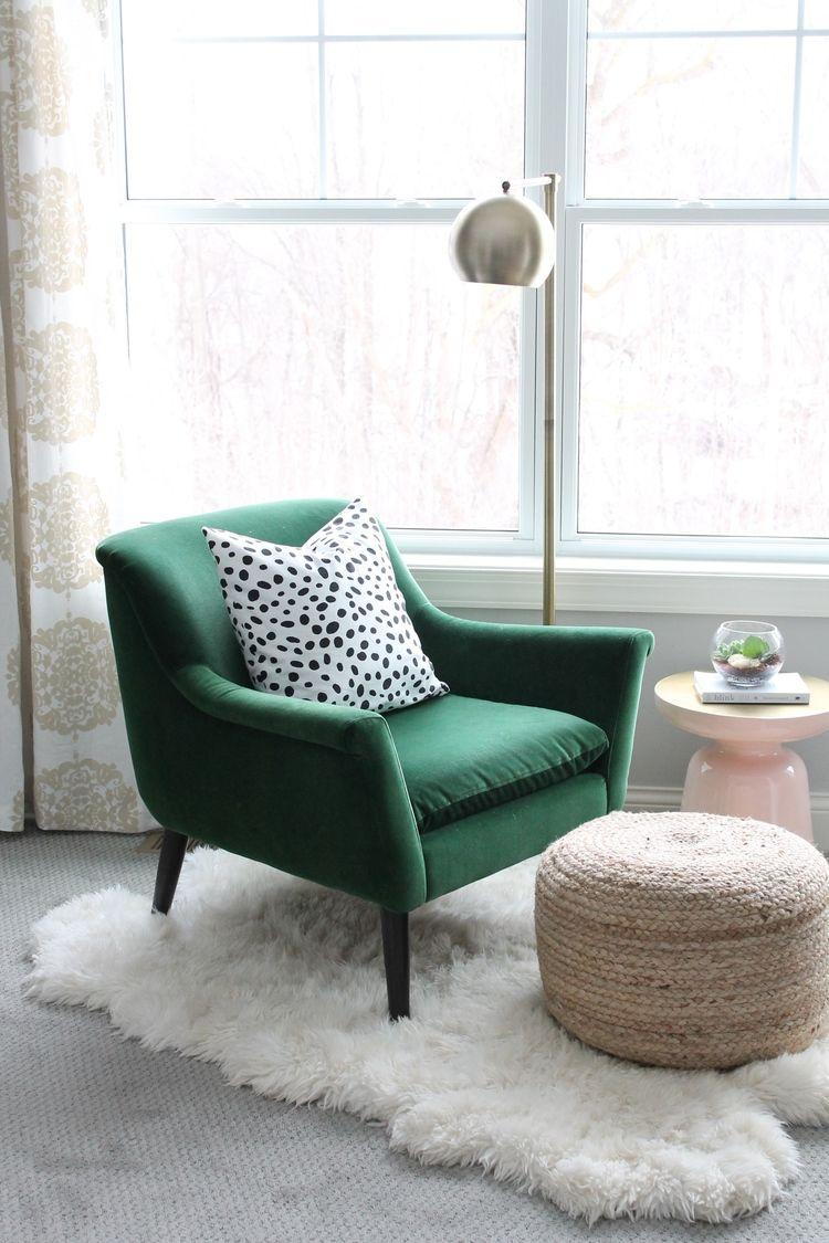 living room chair, green velvet, grey floor, white fur rug, rattan ottoman, golden floor lamp, pink side table