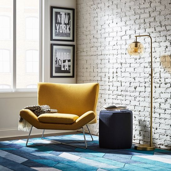 living room chair, yellow, white brick exposed wall, golden floor lamp, dark blue round ottoman, blue patterned rug, white wall