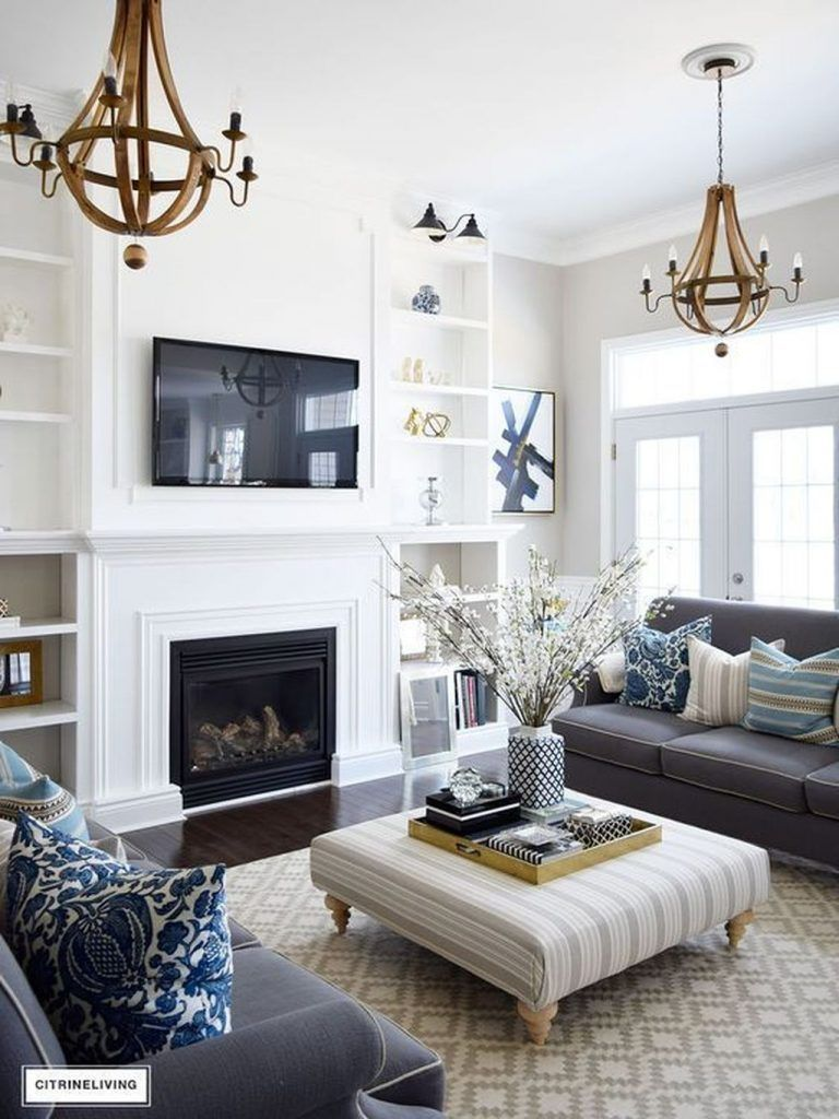 living room, dark wooden floor, neutral patterned rug, white wall, white built in wooden wall, white fireplace, grey sofa, ottoman coffee table, golden chandelier