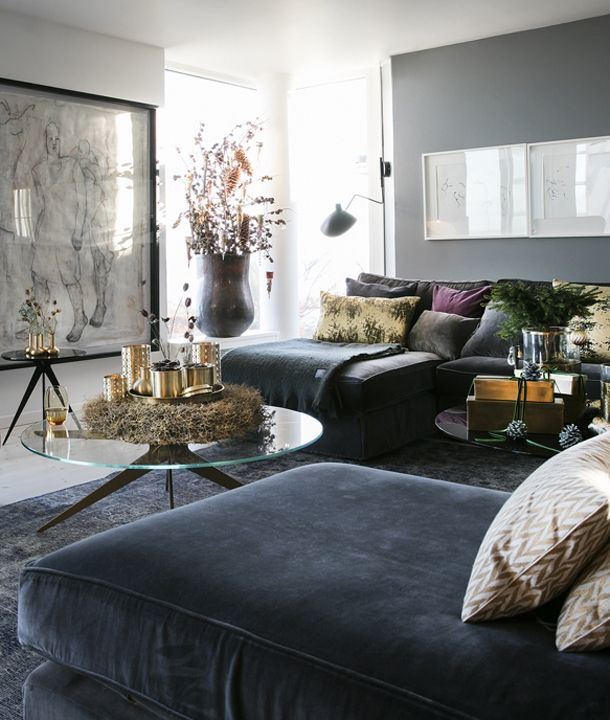 living room, grey floor, black rug, grey velvet lounge chairs, grey wall, white wall, round glass coffee table