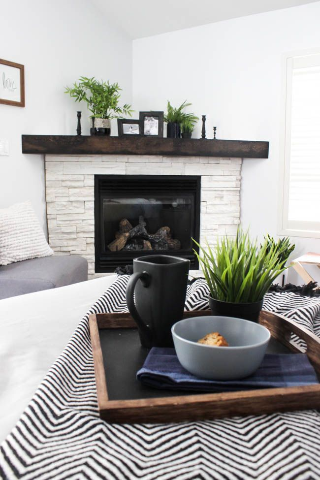 living room, white wall, white brick corner fireplace, black wooden shelves, grey chair