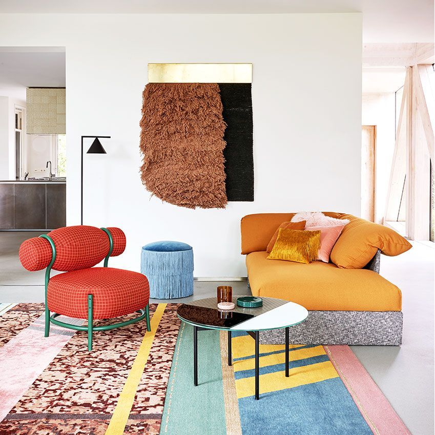 living room, white wooden floor, white wall, yellow sofa, red chair, blue ottoman, round coffee table