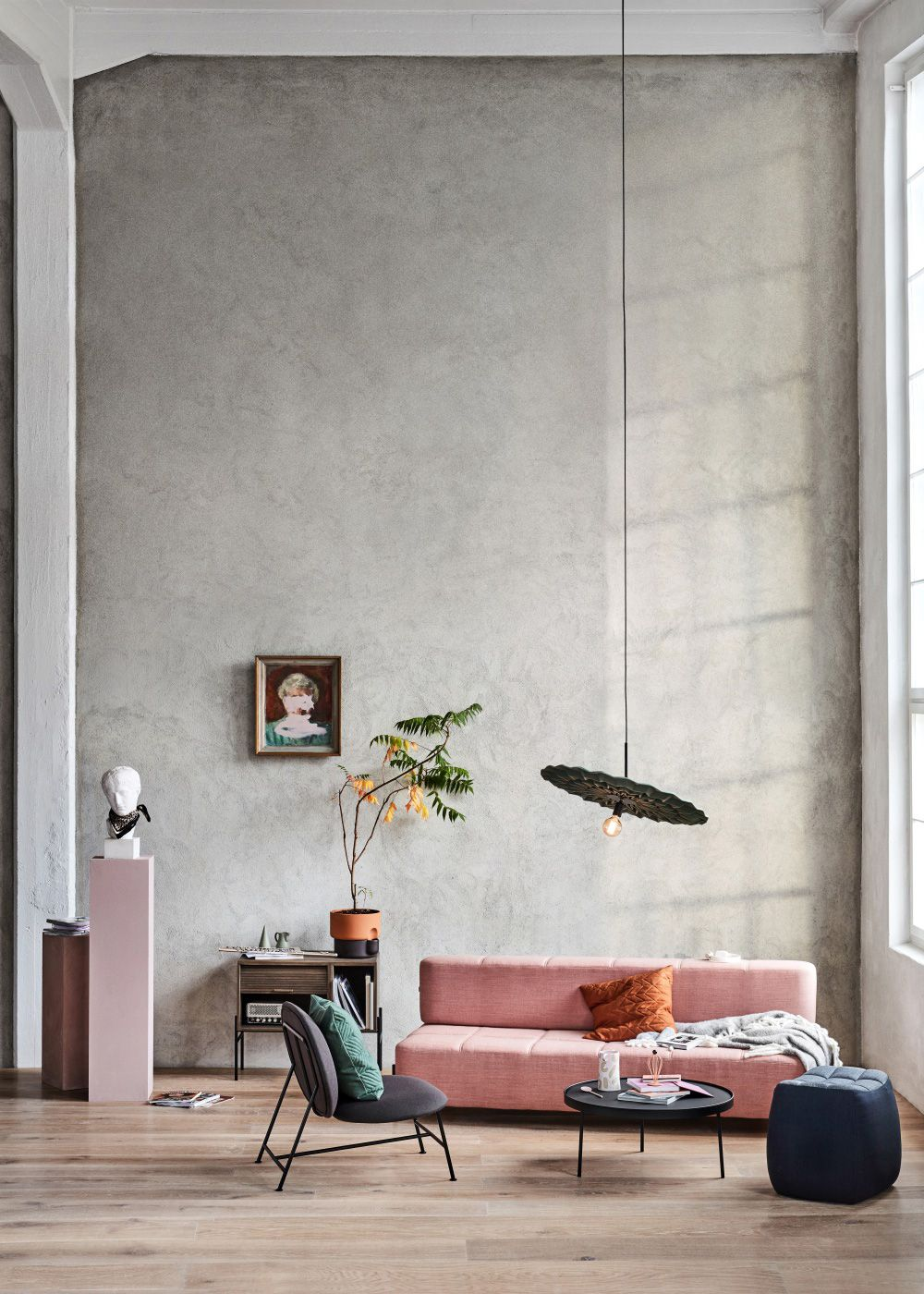 living room, wooden floor, grey seamless wall, low pendant, pink sofa, grey chair, black tray table, grey ottoman