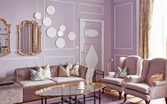 living room, wooden floor, light purple wall, pink chairs, pink sofa, glass coffee table, chandelier, purple rug