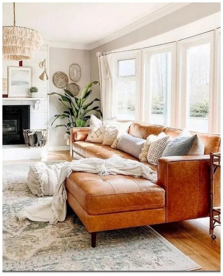 living room, wooden floor, patterned rug, leather sofa, white wall, fringe chandelier, fireplace