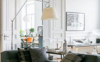 living room, wooden floor, white wall, white door, green tufted sofa, yellow side table, white floor lamp