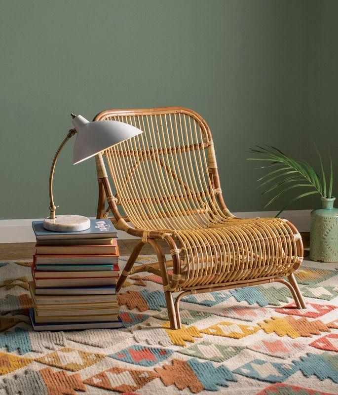 rattan chair, colorful rug, green wall