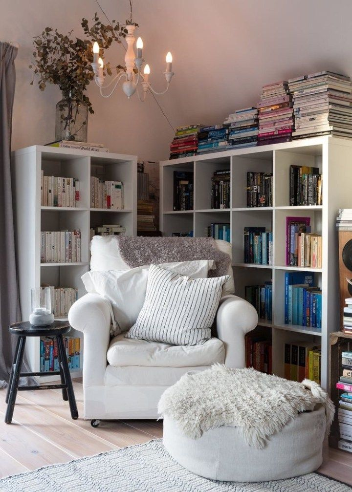 reading nook, wooden floor, white wall, white bookshelves, white chair, white ottoman