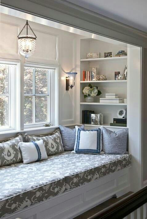 reading spot, white wall, white built in shelves, white built in bench, grey cushion, pendant, sconce
