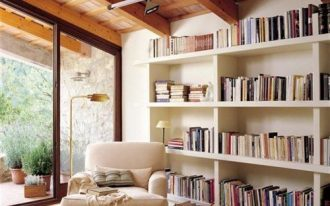 reading spot, wooden floor, white wall, white shelves, wooden ceiling, white lounge char, golden lamp