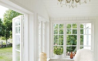 sunroom, brown floor tiles, white wooden wall, white wooden ceiling, chandelier, rattan chair, white wooden framed window, white wooden door