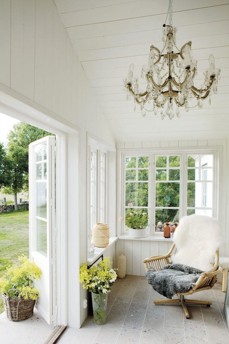 sunroom, brown floor tiles, white wooden wall, white wooden ceiling, chandelier, rattan chair, white wooden framed window, white wooden door