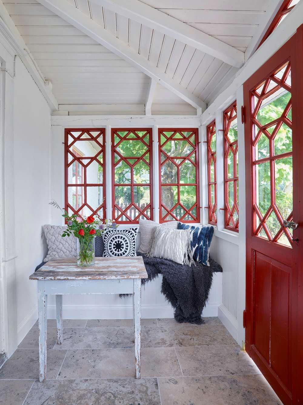 sunroom, grey floor, white wall, white wooden ceiling, red framed window, red door, white built in bench, white pillows