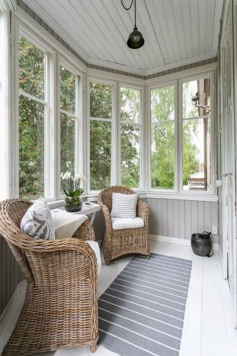 sunroom, white floor, grey shiplank wall, white framed windows, rattan chairs, white floating side table