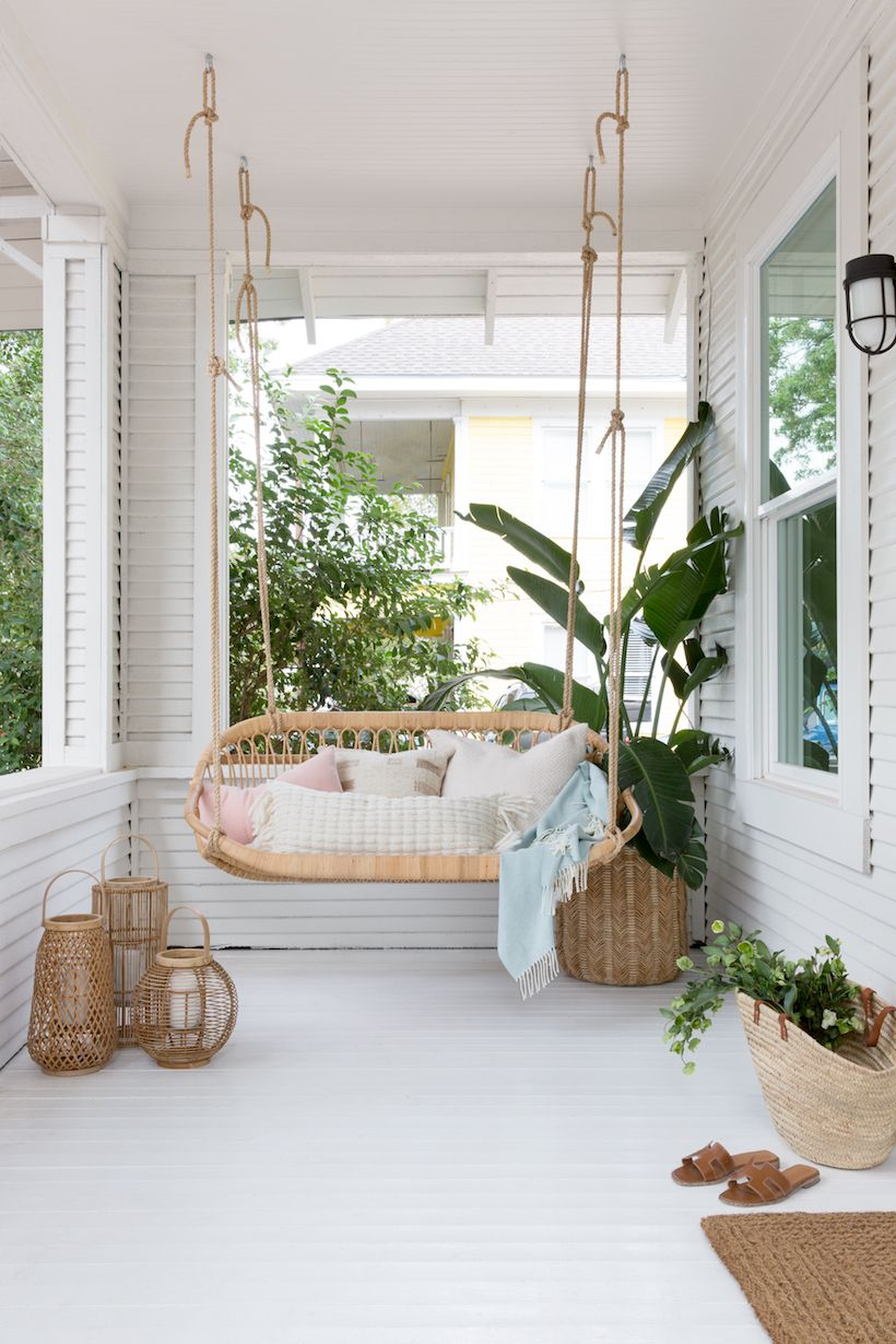sunroom, white wooden floor, white wooden wall, rattan swing sofa, rattan pots, plant, sconce
