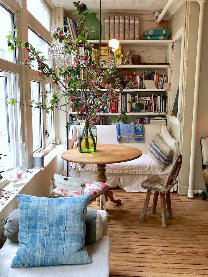 sunroom, wooden floor, white wall, white bench, wooden round table, wooden chair, pendant, built in shelves