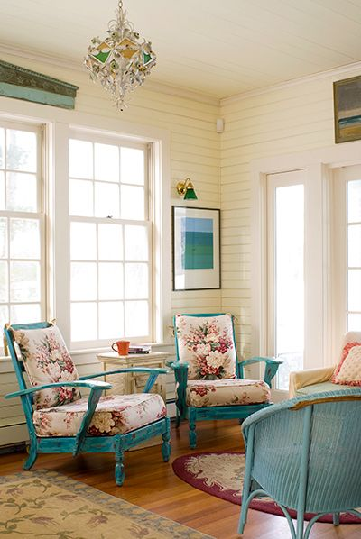 turquoise chair, flowery cushion, turquoise rattan chair, white sofa, wooden floor, white wooden wall