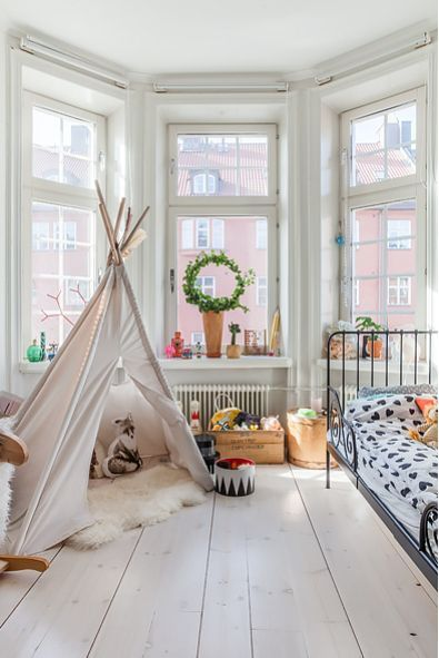 white bedroom in round window bay, white wooden floor, black iron bed, white tent