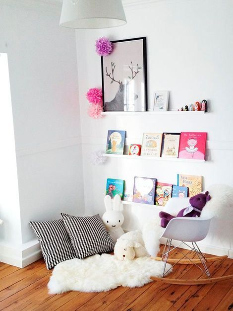 white reading corner, wooden floor, white wall, white wooden display shelves, rocking chair