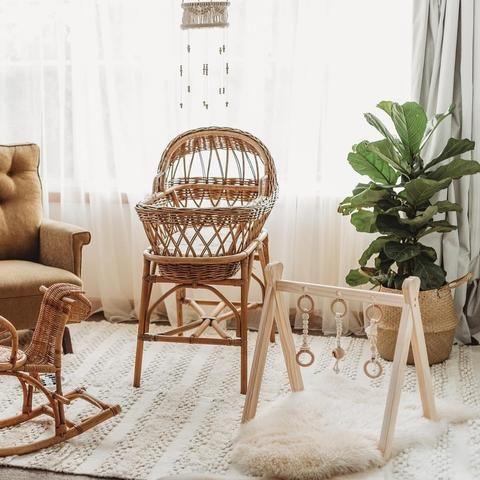 white rug, white curtain, rattan crib, brown chair, wooden toys, rattan toys, rattan plants pot