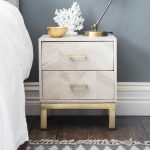 White Wooden Cabinet With Chevron Pattern, Twotier Drawers, Golden Legs, Golden Table Lamp