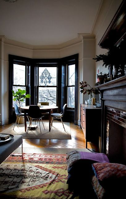 window bay, wooden floor, brown rug, cream wall, black framed window, brown round table, black modern chair