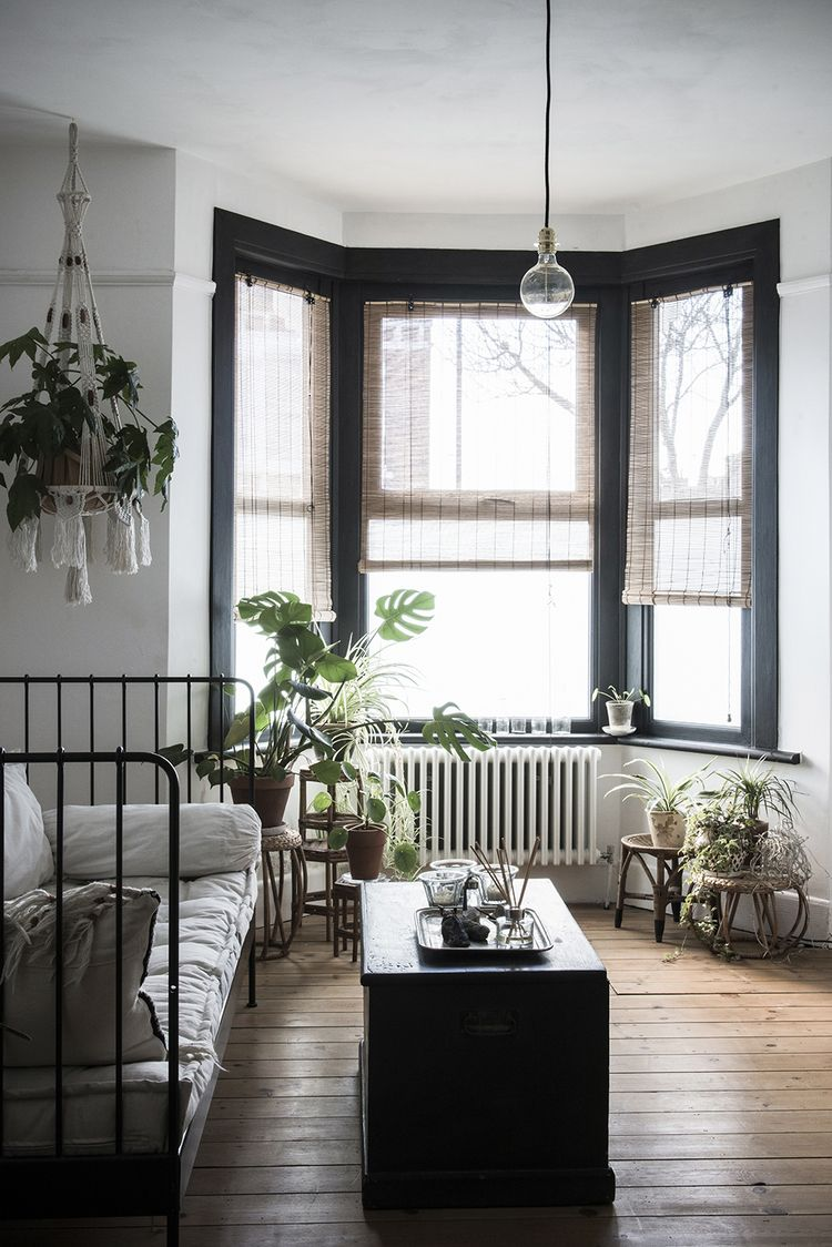 window bay, wooden floor, white wall, black framed window, black iron sofa bed, black wooden coffee table