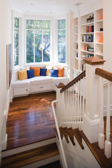 window bay, wooden floor, white wall, white bench with pillows, white built in shelves