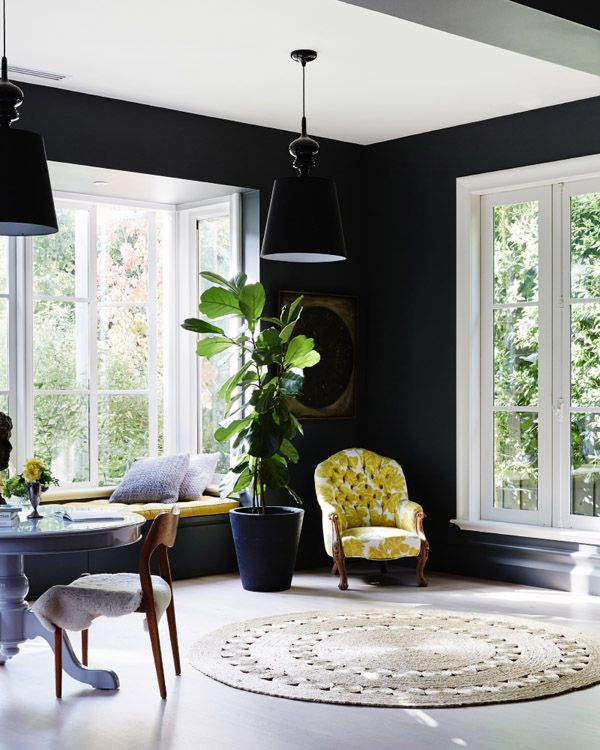 window nook, white floor, black wall, white framed mirror, round table, black window nook, yellow cushion, yellow chairs, black pendant