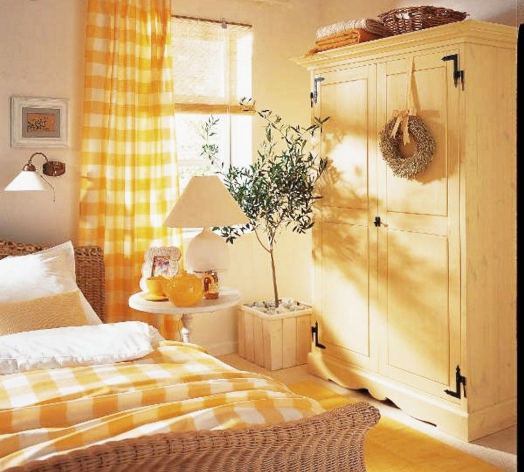 yellow bedroom, woden floor, pastel yellow wall, yellow cabinet, white round side table, wooden plant ot, yellow bedding