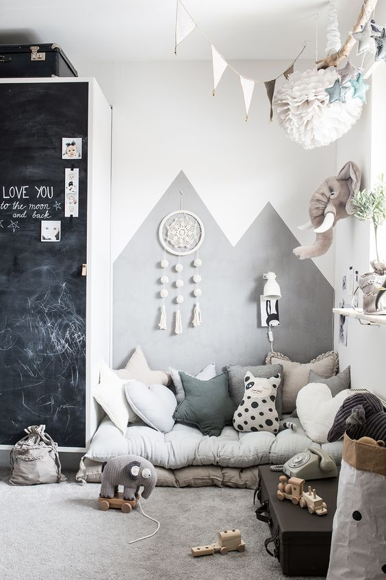 baby room, white wall, white grey cushions, white floating shelves, black suitcases