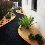 Back Yard, Wooden And Black Stones Line, White Wall, Plants